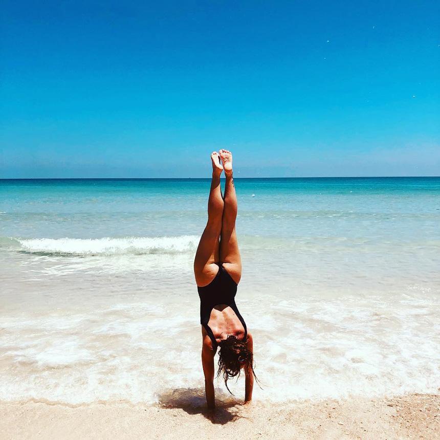 Laurianne qui fait le poirier sur une plage